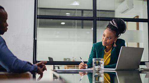 Em um escritório, uma mulher e um homem negros estão sentados um de frente para o outro. A mulher usa tranças amaradas no topo da cabeça, brincos dourados, um blazer verde e uma blusa amarela. Ela está com uma caneta na mão escrevendo em um papel. O homem está de perfil, usando uma camisa azul.